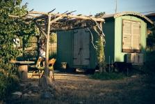 קרון עץ קטן ומשופץ ובו מיטה, מטבחון ושולחן זעיר